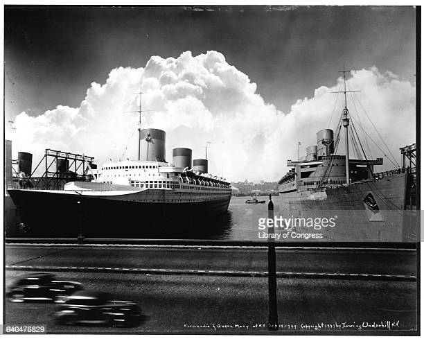 The ocean liners Normandie and Queen Mary moor at piers in New York