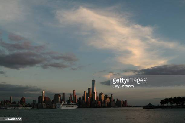 The Oceania Cruises Insignia cruise ship sails in the Hudson River past lower Manhattan and One World Trade Center at sunset in New York City on...