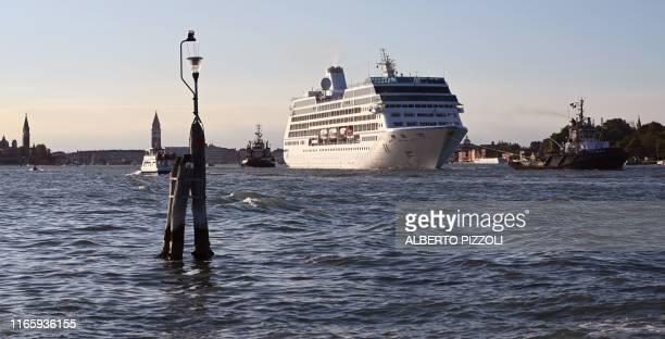 The Oceania Cruises 'Sirena' cruise ship is pulled by three tugboats upon its arrival in the Venice Lagoon in Venice on September 3 as the St Mark's...