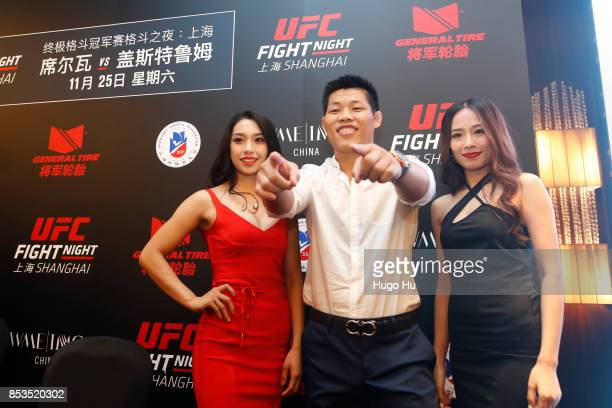 The octagon girl Pan Xiao right Wang jingjing left chinese Li jingliang at the UFC press conference on September 25 2017 in Shanghai China