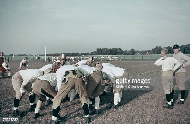 The offense huddles up during a high school football scrimmage circa 1939.