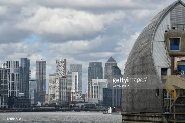 The office buildings in the financial area of Canary Wharf in London are seen behind the Thames Barrier on May 14, 2020. - Britain's economy shrank...