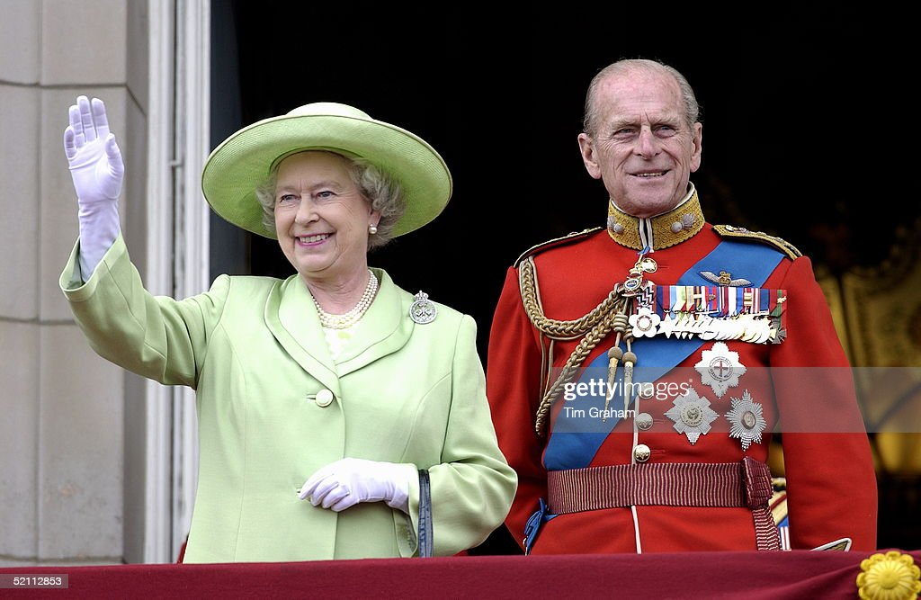 The Official Birthday Of The Queen Is Marked Each Year By A Colourful Military Parade And March-past Known As Trooping The Colour With Troops From The Household Division. Queen Elizabeth Ll Smiling And Waving From The Balcony Of Buckingham Palace With Her Husband, Prince Philip (duke Of Edinburgh), Who Is Wearing The Uniform Of Colonel Of The Grenadier Guards.