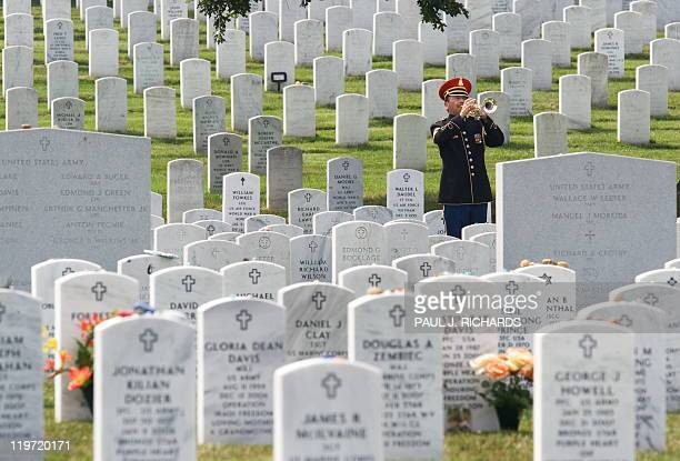 The official Bugler plays taps during the burial of US Army Specialist Anthony M. Lightfoot, of Riverdale, Ga, on August 4 inside Arlington National...