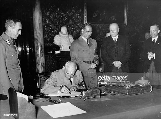 The official ceremony at City Hall in Hamburg Reich Minister Wilhelm Frick signs into the Golden Book of the City of Hamburg Behind him the Reich...