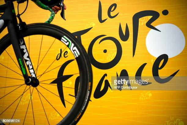 TOPSHOT The official logo of the Tour de France is pictured behind a wheel prior to the start of the 2035 km second stage of the 104th edition of the...