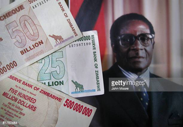 The official portrait of President Robert Mugabe hangs on the wall as Zimbabwaen dollar bank notes are shown June 28 2008 at the airport in Bulawayo...