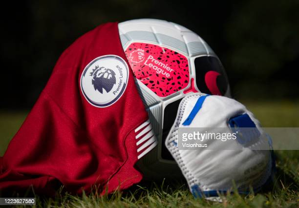 The official Premier League logo on a match ball and Liverpool first team home shirt with a protective face mask on May 4, 2020 in Manchester, England