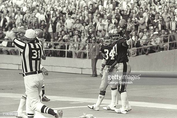 The official signals no catch as defensive back Mel Blount of the Pittsburgh Steelers holds up the ball after nearly intercepting a pass during a...