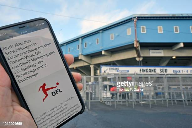 The official statement of the German Football League to postpone every match of the Bundesliga weekend is shown on a mobile phone prior to the...