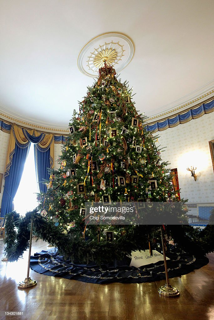The official White House Christmas tree, the centerpiece of the Blue Room, is on display during the first viewing of the 2011 White House Christmas decorations November 30, 2011 in Washington, DC. Honoring Blue Star families, the 18-foot 6-inch balsam fir tree is decorated with framed military medals and handmade holiday cards created by military children living on installations around the world. The theme, 'Shine, Give, Share,' runs throught the White House with a 400-pound White House Gingerbread House and 37 Christmas trees.