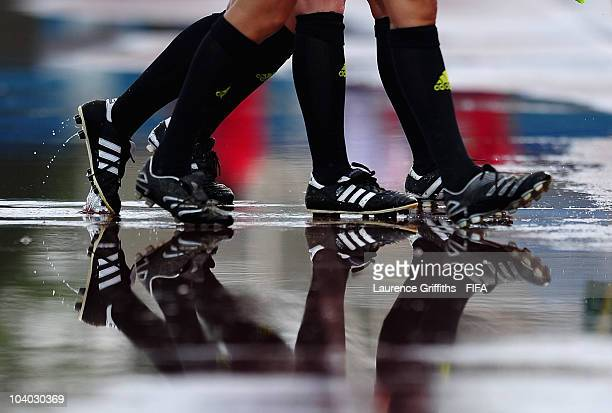 The Officials leave the field through puddles after a heavy storm during the FIFA U17 Women's World Cup Group B match between Mexico and South Africa...