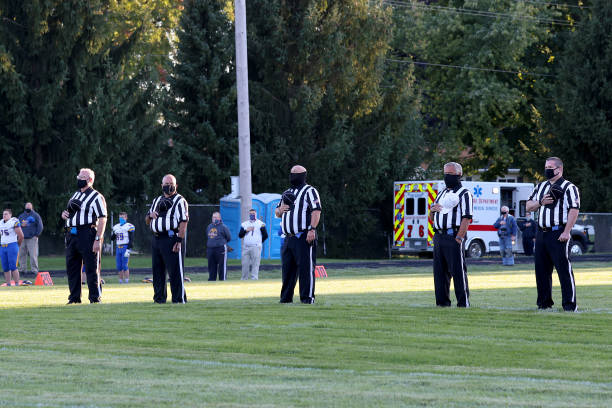The officials on the field during the national anthem wearing mask between the Ida Bluestreaks and the Clinton Redskins on September 18, 2020 in...