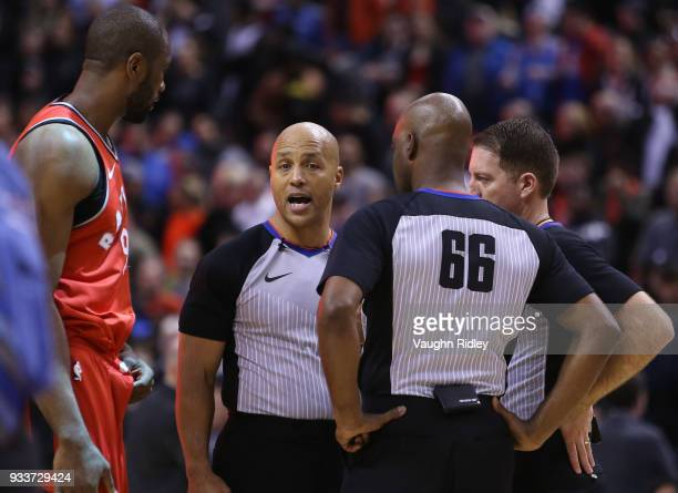 The officiating crew of Marc Davis Haywoode Workman and Brent Barnaky talk to Serge Ibaka of the Toronto Raptors during the second half of an NBA...