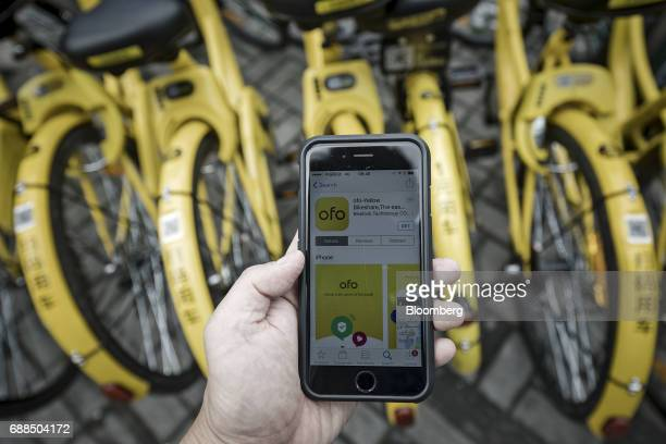 The Ofo Inc bicyclesharing app is seen on a smartphone in front of the company's bikes parked on a sidewalk in Shanghai China on Thursday May 25 2017...