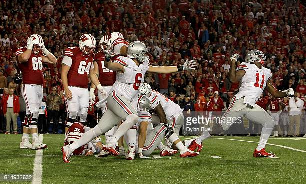 The Ohio State Buckeyes celebrate after sacking Alex Hornibrook of the Wisconsin Badgers to end the game in overtime at Camp Randall Stadium on...
