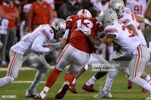 The Ohio State Buckeyes defense swarms quarterback Tanner Lee of the Nebraska Cornhuskers at Memorial Stadium on October 14 2017 in Lincoln Nebraska