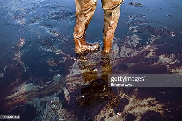 The oil covered waiters of a photographer are seen along the crude oil covered shore on June 9 2010 on Grand Terre Island Louisiana