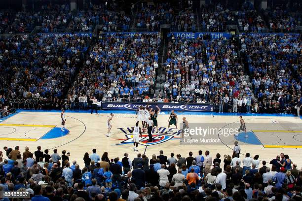 The Oklahoma City Thunder starting line up complete their first tip off as fans filling the arena watch the inaugural game against the the Milwaukee...