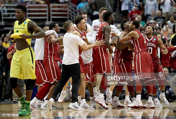 The Oklahoma Sooners celebrate their 8068 victory as Jordan Bell of the Oregon Ducks walks off the court in the NCAA Men's Basketball Tournament West...