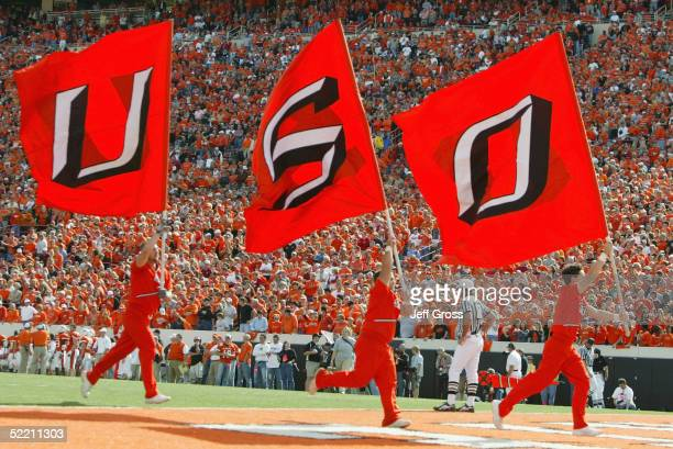 The Oklahoma State University Cowboys Cheerleading Squad carries huge OSU flags during the game against the University of Oklahoma Sooners at Boone...