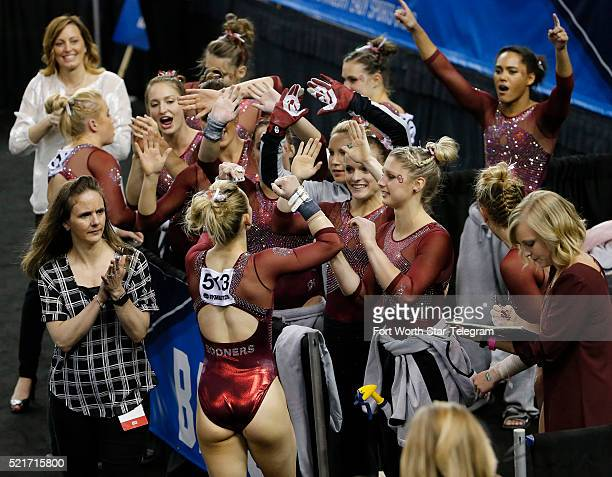 The Oklahoma team greets Haley Scaman after her uneven parallel bars routine in the Super Six finals of the NCAA Women's Gymnastics Championships at...