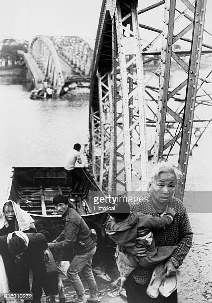 The old and the young flee Tet offensive fighting in Hue managing to reach the south shore of the Perfume River despite this blown bridge 1968  ...