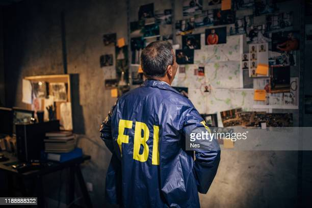 the old detective works alone late at night in his office - fbi stock pictures, royalty-free photos & images