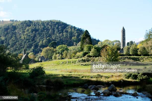 the old irish cemetery and round tower in glendalough (county wicklow, ireland) - irish round tower stock photos and pictures