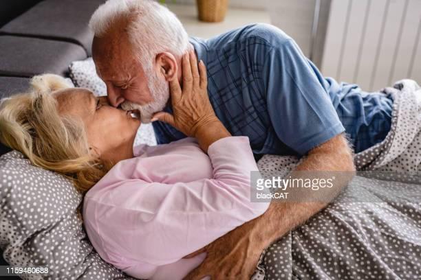 la vieja pareja se besa en la cama. - masturbacion fotografías e imágenes de stock