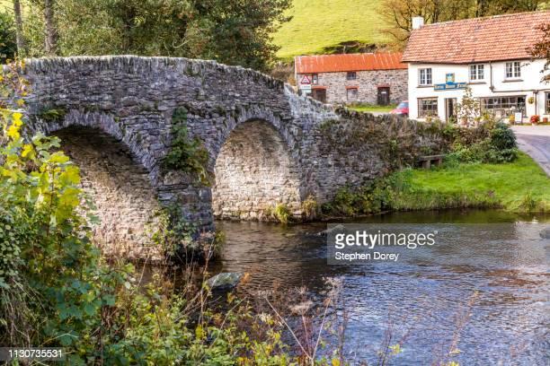 the old stone packhorse bridge over badgworthy water beside lorna doone farm in the village of malmsmead, devon uk. - exmoor national park 個照片及圖片檔