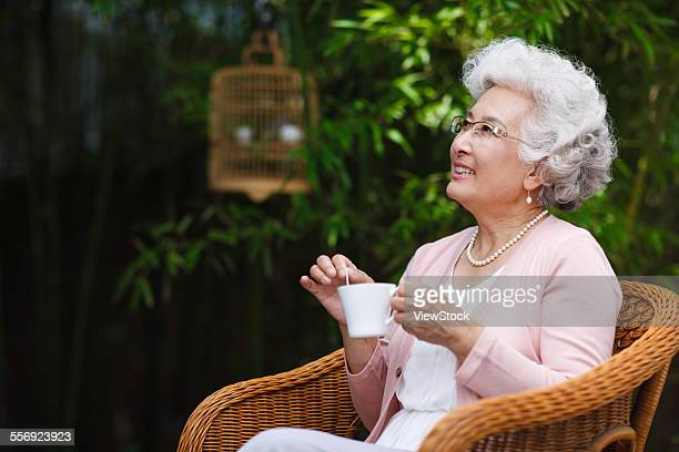 the old woman to drink coffee in the garden - coffee drink stock pictures, royalty-free photos & images