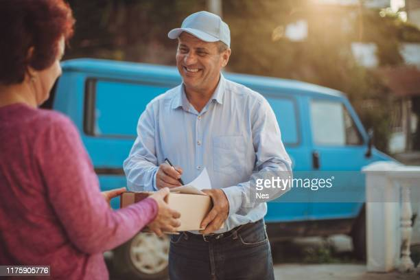 the older delivery man delivers the mail - uniform cap stock pictures, royalty-free photos & images