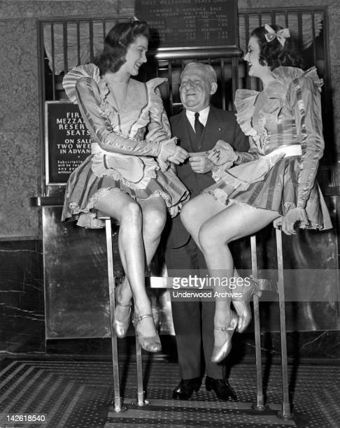 The oldest patron of Radio City Music Hall is shown here purchasing the 50000th ticket sold from two of the Rockettes New York New York early to mid...