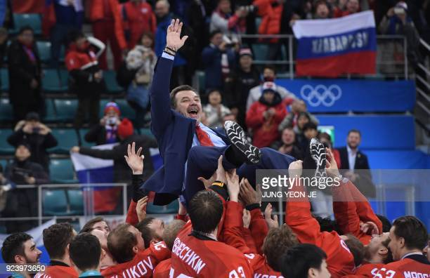 The Olympic Athletes from Russia's head coach Oleg Znarok is carried by his players after the medal ceremony after they won the men's gold medal ice...