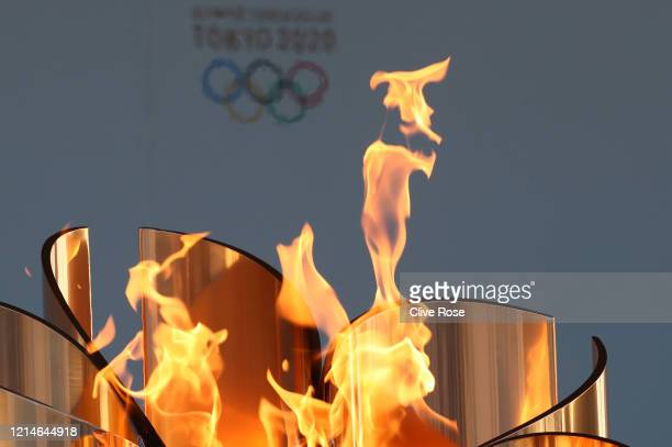 The Olympic cauldron is lit during the 'Flame of Recovery' special exhibition at Aquamarine Park a day after the postponement of the Tokyo 2020...