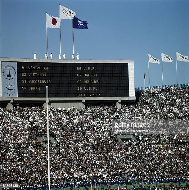 The Olympic fflag flies over the scoreboard showing the list of the parade of Nations during the opening ceremonies for the XVIII Olympiad at the...
