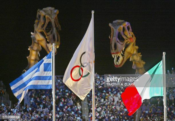 The Olympic flag flies between the Greek and Italian flags as giant dinosaur skeletons look at them during the closing ceremony of the XIXth Winter...