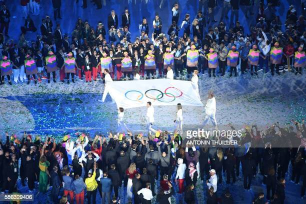 The Olympic flag is carried before being raised during the opening ceremony of the Rio 2016 Olympic Games at the Maracana stadium in Rio de Janeiro...