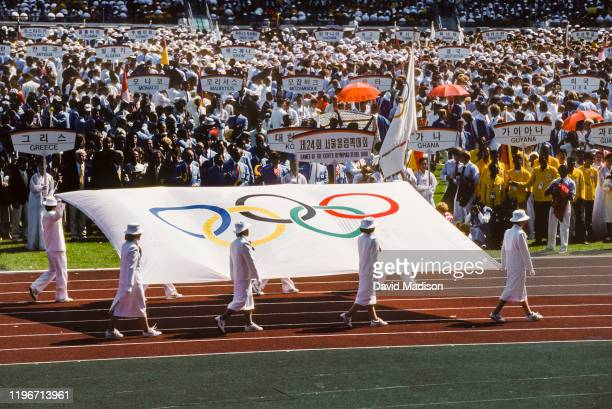 The Olympic Flag is carried into the stadium during the Opening Ceremony of the 1988 Olympic Games on September 17, 1988 at the Jamsil Olympic...