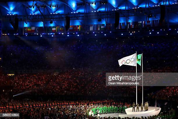 The Olympic flag is hoisted next to the Brazilian national flag during the Opening Ceremony of the Rio 2016 Olympic Games at Maracana Stadium on...