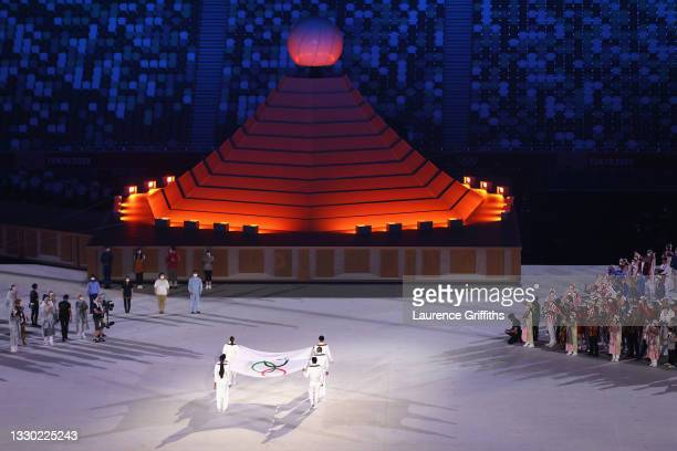 The Olympic flag is raised alongside the Japanese flag with the Olympic Cauldron during the Opening Ceremony of the Tokyo 2020 Olympic Games at...