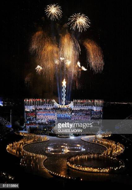 The Olympic Flame and fireworks illuminate the night sky 08 February 2002 during the opening ceremonies of the XIXth Winter Olympics at the Rice...