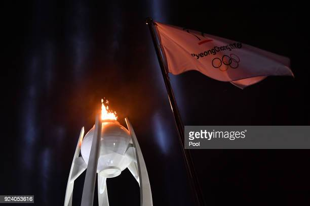 The Olympic flame burns behind the PyeongChang Olympic flag during the Closing Ceremony of the PyeongChang 2018 Winter Olympic Games at PyeongChang...