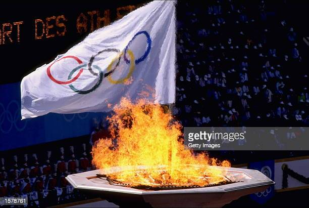 The Olympic flame burns brightly as the Olympic flag waves behind it during the opening ceremony of the 1988 Olympic Games in Seoul South Korea The...