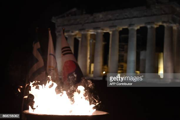 The Olympic Flame burns in front of the ancient temple of Parthenon atop the Acropolis hill in Athens during the torch relay on October 30 2018 for...