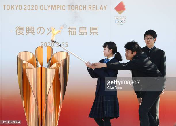 The Olympic flame is lit at the cauldron during the 'Flame of Recovery' special exhibition ceremony at Aquamarine Park a day after the postponement...