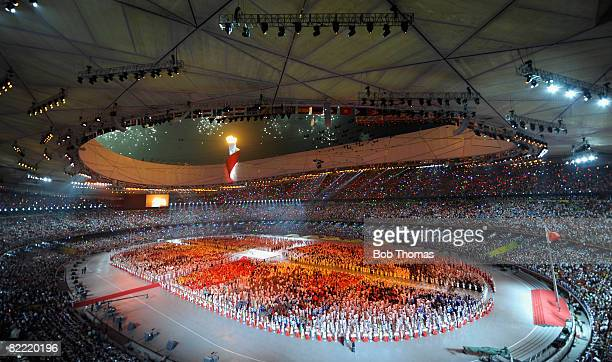 The Olympic Flame is lit high over the stadium at the end of the Opening Ceremony for the Beijing 2008 Olympic Games at the National Stadium on...
