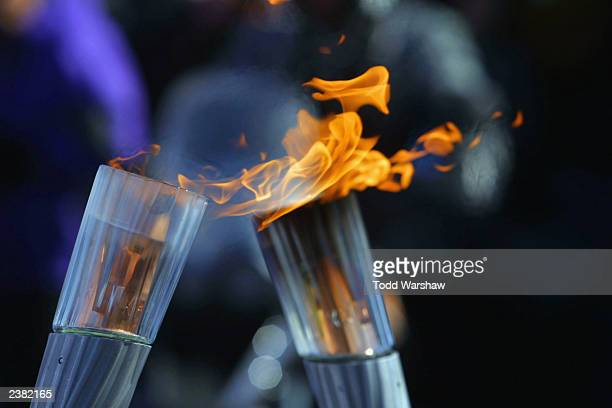The Olympic Flame is passed between two torches during the 2002 Salt Lake City Olympic Torch Relay on February 8 2002 in Taylorsville Utah