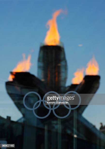 The Olympic flame is seen in the reflection of a window with the Olympic rings etched into it during day 9 of the Vancouver Winter Olympic Games on...